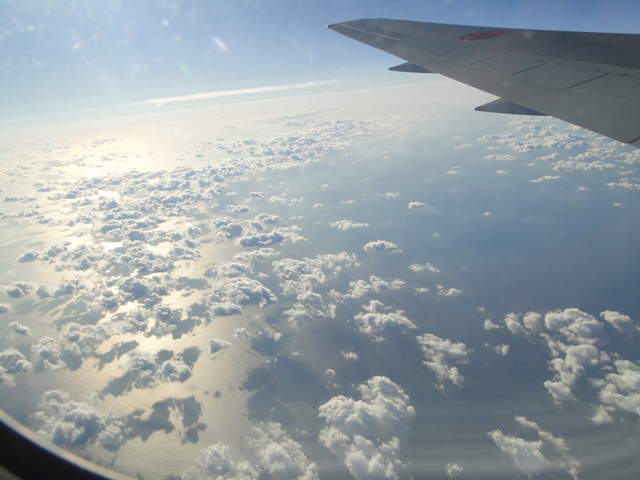 機内からの景色 細かい雲の間から海と海に映る雲の陰